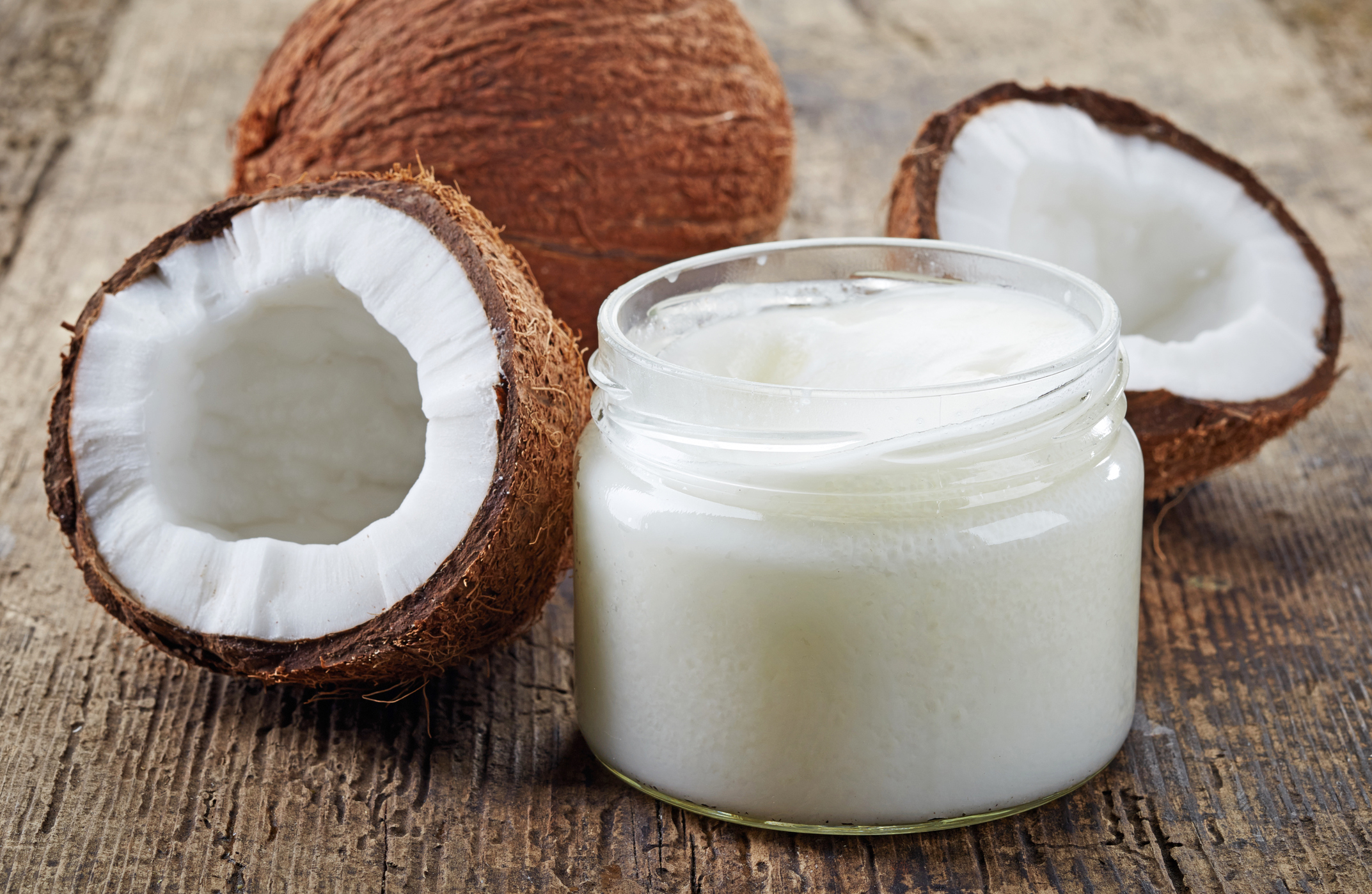 Fresh coconuts and a jar of coconut oil on a wooden table